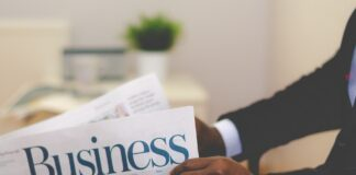 hands holding a business newspaper