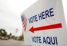 Yard sign that says Vote Here, Vote Aqui