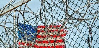 US flag behind fence