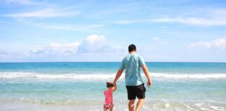 man walking with baby on beach