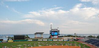 people sitting on the field at wahoos stadium