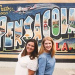 two women standing in front of a Pensacola mural