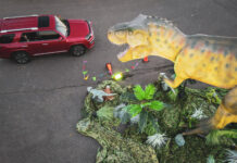 dinosaur looking at car