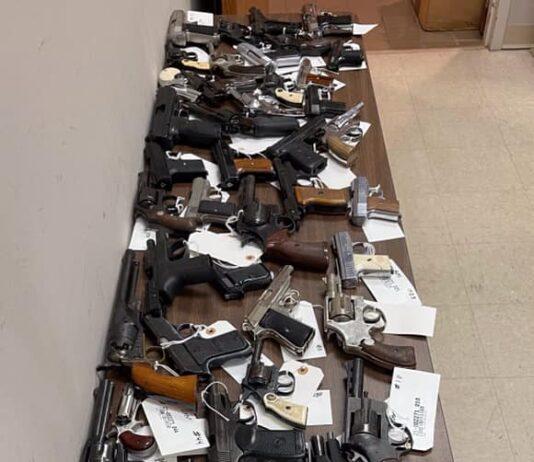Dozens of hand guns on a table