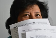 woman holding income tax return forms