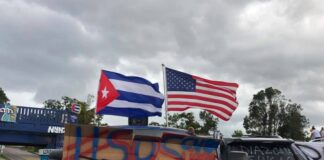 Cuban and American flags waving above a truck