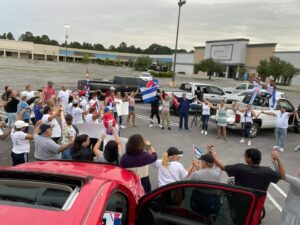 People standing in a circle holding hands and the Cuban flag